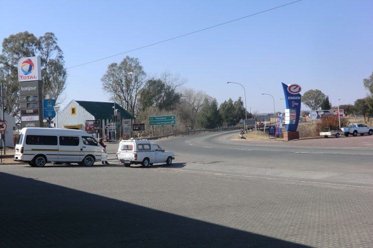 """Links im Bild eines der berüchtigten Minibus-Taxis. Kommentar meiner Betreuerin vorab: """"  Please remember that in South Africa our public transport are NOT as safe as what you are used to! We prefer that you do NOT make use of minibus taxi's.  They  are not safe and the drivers are reckless and some of them do not have  valid drivers licenses."""" Genutzt werden sie fast ausschließlich von der schwarzen Bevölkerung. Es gibt keine festen Routen (angehalten wird, sobald einer der Fahrgäste """"Thank you"""" ruft; in JHB halten sie dann wohl manchmal auch mitten auf großen Kreuzungen an) und keine festen Fahrpläne (losgefahren wird, wenn der Bus voll ist)."""