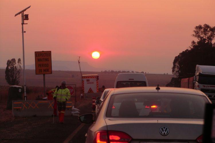 Sonnenauf(!)gang auf dem Weg zur Mine. Bei Baustellen auf Highways wird eine Richtung komplett gesperrt und der Verkehr abwechselnd über die andere Spur gelenkt. Daher das freudebringende Schild.