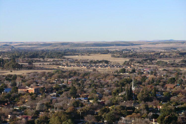 """Bloemfontein von oben. Ca. in der Bildmitte sieht man die vollendete Form der gated community: """"Viele wohlhabende Südafrikaner aller Hautfarben ziehen in Compounds  genannte Vororte. Solche Wohnviertel haben eine eigene  Infrastruktur mit Geschäften und Schulen, sind rundum mit hohen Zäunen  abgesperrt und werden rund um die Uhr von privaten Sicherheitsdiensten  bewacht. Auch Elektrozäune sind sehr häufig."""" (wikipedia)"""
