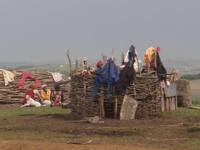 Als wir an der Hütte des herbalist ankamen, trafen wir nur seine Mutter an, da er gerade beim Fischen war. Er hatte das Handy nicht gehört, das ihn von unserer Ankunft in Kenntnis setzen sollte. Im Vordergrund der Nacht-Unterstand der Hühner, im Hintergrund der Holzstapel, der den Brennstoff zum Kochen liefert. Das gesammelte Holz wir gut sichtbar vor der Hütte aufgestapelt, da eine Frau ohne Holz vor der Hütte von den anderen Frauen im Dorf als faul angesehen wird.