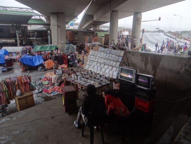 Auf dem Victoria Street Market in Durban. Im Vordergrund der Stand verkauft Videos und Musik, die zur Anschauung auf den Röhrenfernsehern abgespielt werden. Die schlechte Bildqualität wird dabei durch Lautstärke kompensiert, was bei zehn Ständen nebeneinander zu einem Lärmpegel führt, der in deutschen Diskotheken vermutlich wegen akuter Gesundheitsgefährdung verboten wäre.
