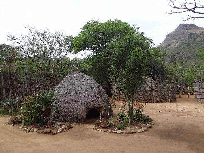 In Swasiland: Die sogenannte Bienenkorbhütte war die traditionelle Behausung, ist heute aber nur noch selten zu sehen. Der Berg im Hintergrund wurde zu Zeiten, als Swasiland noch britisches Protektorat war, für Hinrichtungen genutzt. Verurteilte wurden mit verbundenen Augen und Händen in die Tiefe gestürzt.