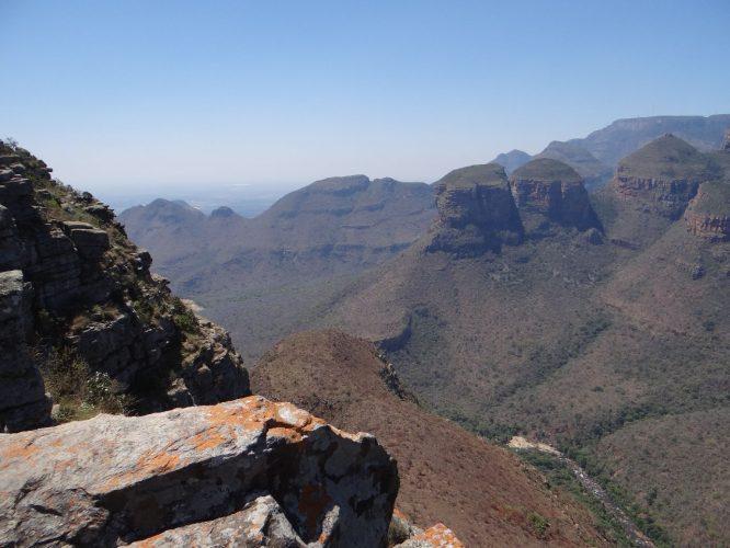 Zu sehen ist der Blyde River Canyon, der drittgrößte Canyon der Welt (und der größte grüne). Im Hintergrund sind die Three Rondavels (die Felsen ähneln den traditionellen Hütten ).