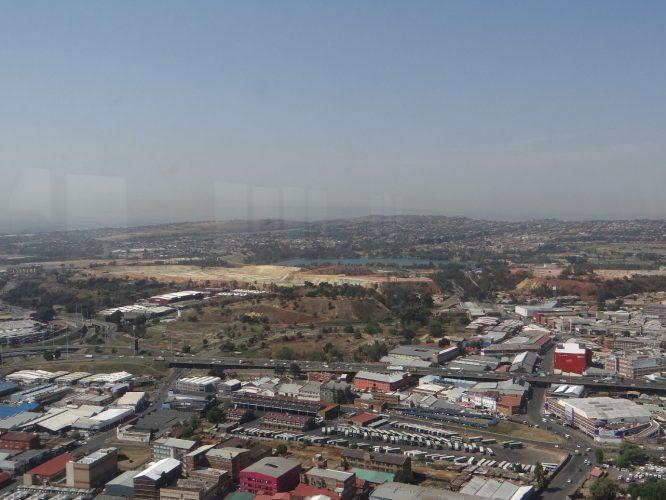 Blick über Johannesburg von Afrikas höchstem Gebäude. In der Bildmitte eine ehemalige Goldmine, die offziell inzwischen stillgelegt ist. Allerdings gibt es nach wie vor viele Leute, die dort illegal graben. Letztes Jahr kamen 50 bis 60 dabei ums Leben.