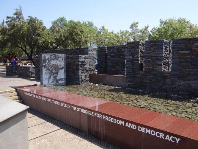 An dieser Stelle wurden bei einer Schülerdemonstration gegen die Einführung von Afrikaans als Unterrichtssprache 1976 zahlreiche Jugendliche von der Polizei erschossen, der jüngste war 12 Jahre alt. Das Foto im Hintergrund ging um die Welt und zeigte die Schrecken des Apartheid-Regimes.