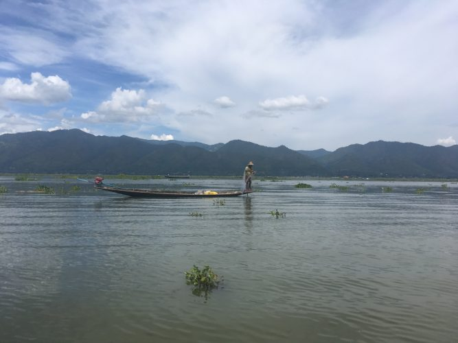 The emblematic picture of Lake Inle: Fishermen balancing on the tip of their boat to put the net into the water.