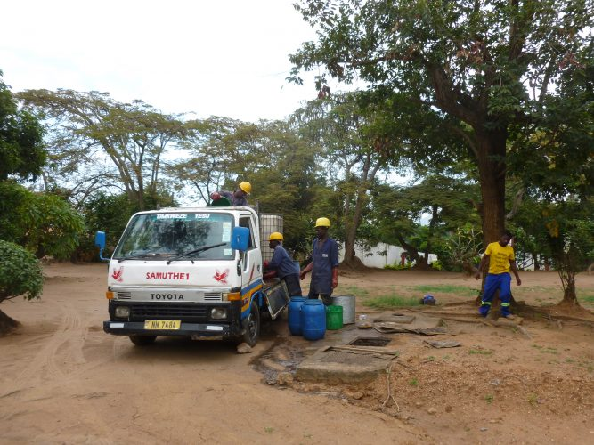 Here we see the emptying of a septic tank which is buried underground and can be accessed and emptied through the hole. Much more comfortable than emptying a pit latrine.