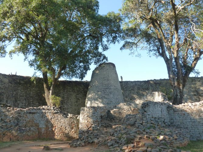 """This is part of Great Zimbabwe, a medieval city built between the 11th and 15th century. It's the largest manmade structure from pre-colonial times in Sub-Saharan Africa. The site gave the country its name after independence, Zimbabwe meaning """"Big House of Stone"""". This tower is the most emblematic structure of the site and is now used as the symbol of the ruling party ZANU PF, along with the two trees on the side."""